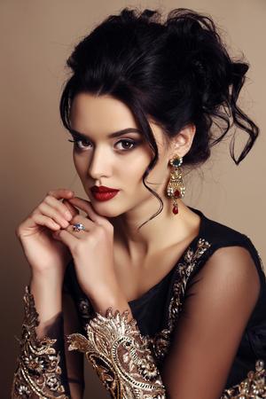 fashion studio photo of gorgeous woman with dark hair wears luxurious  dress and precious bijou