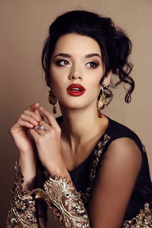 fashion studio photo of gorgeous woman with dark hair wears luxurious dress and precious bijou