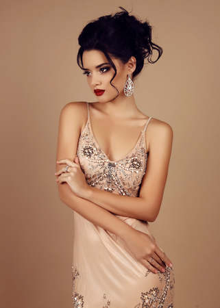 party outfit: fashion studio photo of gorgeous woman with dark hair wears luxurious sequin dress and precious bijou