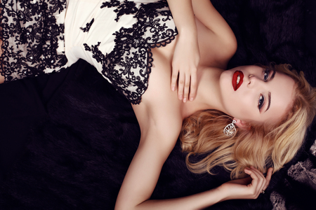 party outfit: fashion studio photo of gorgeous sensual woman with blond hair and evening makeup,wears luxurious party dress and precious bijou,lying on fur coat Stock Photo