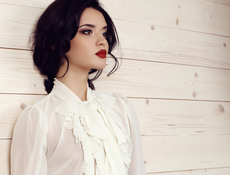 fashion studio photo of gorgeous young woman with dark hair and evening makeup,wears elegant white blouse Banco de Imagens - 48368246