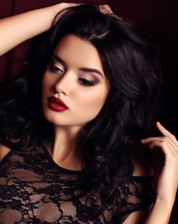 black hair: fashion studio photo of gorgeous young woman with dark hair and evening makeup, wears luxurious black lace dress