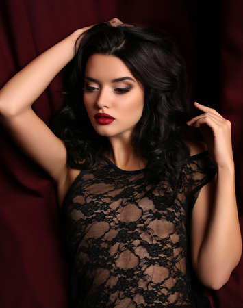 gorgeous girl: fashion studio photo of gorgeous young woman with dark hair and evening makeup, wears luxurious black lace dress