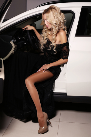 blonde woman: fashion photo of gorgeous woman with long blond hair wears luxurious dress,posing in white car