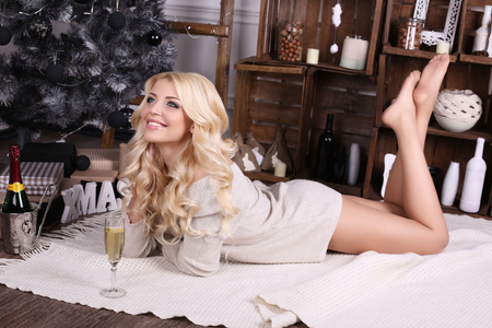 young tree: fashion interior photo of beautiful young woman with blond hair and charming smile, wears cozy knitted cardigan, posing beside Christmas tree and presents  with glass of champagne