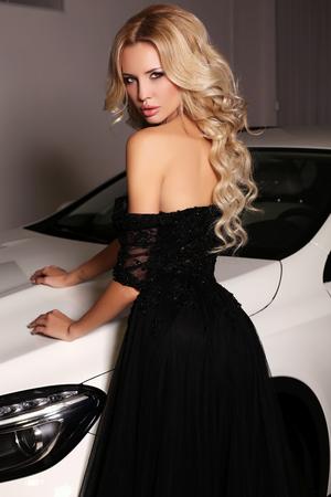 hair blond: foto di moda donna bellissima con lunghi capelli biondi indossa abiti di lusso, in posa accanto macchina bianca