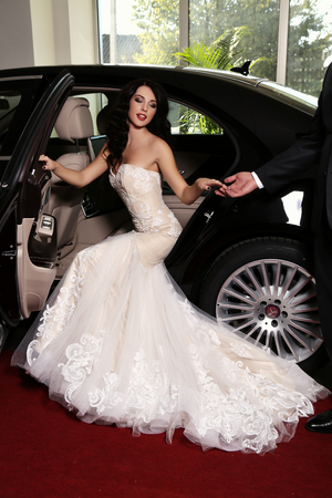 lady in red: fashion photo of gorgeous woman with dark hair wears luxurious dress,posing in black car, arrived on red carpet event Stock Photo
