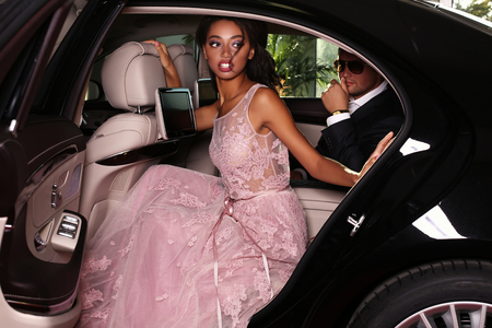 mulatto woman: fashion photo of gorgeous mulatto woman with long dark hair wears luxurious dress and man in elegant costume,arrived on red carpet event in black car