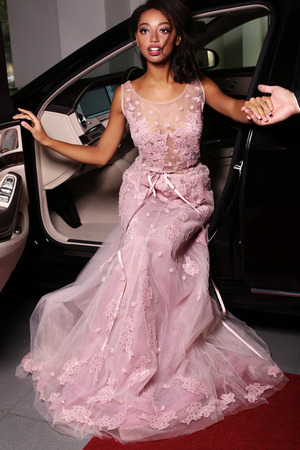sexy fashion: fashion photo of gorgeous mulatto woman with long dark hair wears luxurious dress,arrived on red carpet event in black car