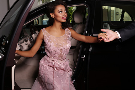 red carpet event: fashion photo of gorgeous mulatto woman with long dark hair wears luxurious dress,arrived on red carpet event in black car