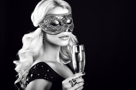 beautiful black woman: black and white fashion photo of beautiful young woman with blond hair, wears elegant black dress and carnival mask on face,posing  with glass of champagne in studio