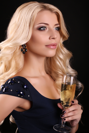 gorgeous girl: fashion photo of beautiful young woman with blond hair, wears elegant black dress,posing  with glass of champagne in studio