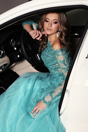 luxurious: fashion photo of gorgeous woman with long blond hair wears luxurious dress,posing in white car