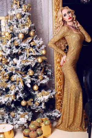 christmas woman: fashion interior photo of beautiful sensual woman with blond hair in luxurious golden dress posing beside a Christmas tree Stock Photo