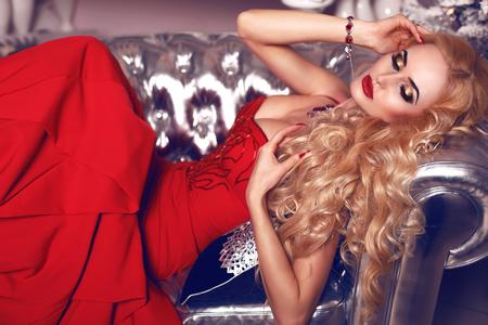 mujeres elegantes: Foto de la moda interior de la mujer sensual hermosa con el pelo rubio en un elegante vestido rojo posando en el interior de lujo blanco Foto de archivo