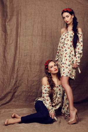 headbands: moda foto de estudio de dos hermosas chicas con el pelo oscuro en vestidos con estampados de amapolas rojas y con vinchas