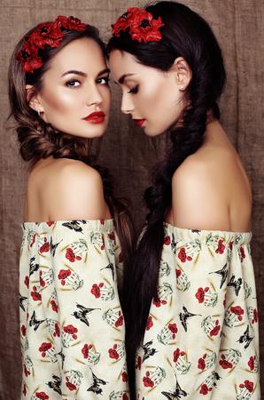 mode studio foto van twee mooie meisjes met donker haar in jurken met prints van rode klaprozen en hoofdbanden
