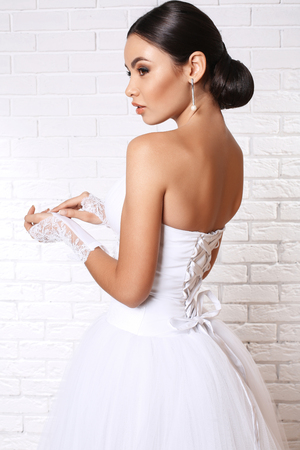 lace gloves: fashion studio portrait of beautiful young bride with dark hair in elegant wedding dress and lace gloves