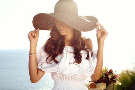fashion outdoor photo of beautiful sensual girl with dark hair in elegant dress and hat riding by summer beach