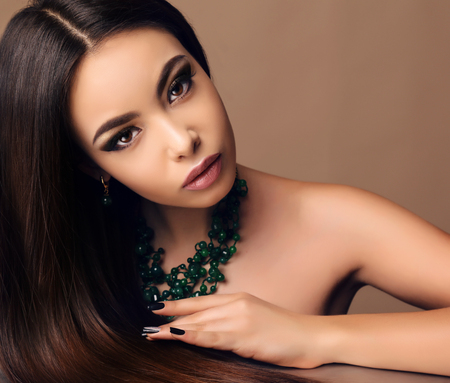 glamour hair: fashion portrait of beautiful sensual woman with dark straight hair with bright makeup and necklace Stock Photo