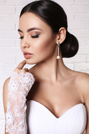 fashion studio photo of beautiful bride with dark hair wearing elegant wedding dress and accessories