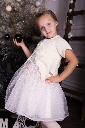 niño modelo: fiesta de la foto de la hermosa niña linda con el pelo rubio uso del traje elegante, presenta al lado del árbol de navidad con los presentes