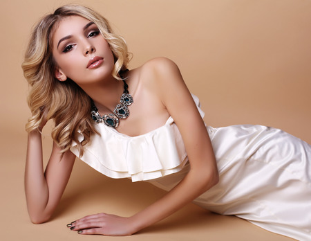 capelli biondi: fashion studio photo of beautiful young woman with blond curly hair and evening makeup,wears elegant white dress and luxurious necklace