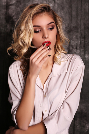 style woman: fashion studio photo of beautiful young woman with blond curly hair and evening makeup,wears elegant white shirt