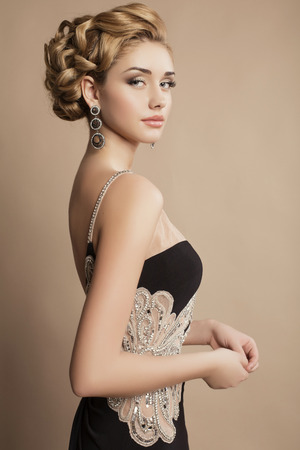 fashion studio photo of beautiful young woman with blond curly hair and evening makeup,wears luxurious party dress and bijou