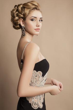mode studio foto van mooie jonge vrouw met blond krullend haar en avond make-up, draagt luxe feestjurk en bijou Stockfoto