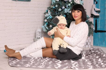 christmas toy: holiday tender photo of beautiful mother with dark hair with cute little baby sitting  beside Christmas tree