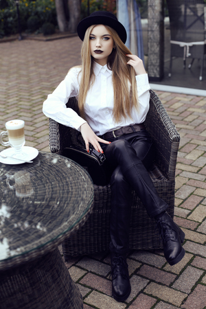 tomando café: calle de la moda joven mujer look.beautiful con pelo largo y liso lleva ropa elegante con accesorios, el consumo de café en café al aire libre Foto de archivo