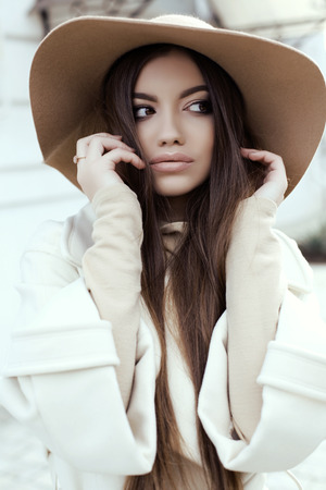 glamour hair: fashion street outfit, beautiful glamour girl with dark straight hair wears luxurious beige coat with elegant hat