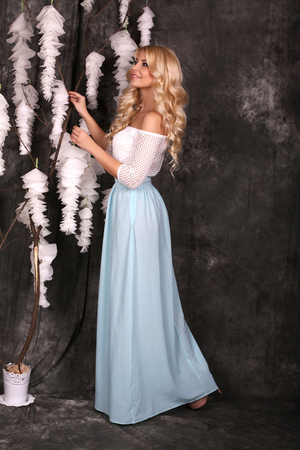 glamour hair: fashion studio photo of beautiful charming woman with long blond hair wears elegant dress beside deco flowers