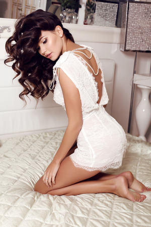 woman dress: fashion interior photo of beautiful sensual woman with long dark hair wears elegant lace suit,posing at bedroom Stock Photo
