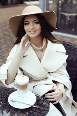 sexy glamour: fashion street outfit, beautiful glamour girl with dark straight hair wears luxurious beige coat with elegant hat,drinking coffee in outdoor cafe Stock Photo