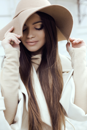 chic: fashion street outfit, beautiful glamour girl with dark straight hair wears luxurious beige coat with elegant hat walking by the street Stock Photo