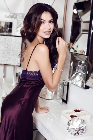 fashion interior photo of beautiful sensual woman with long dark hair wears elegant silk dress, posing at luxurious bedroom