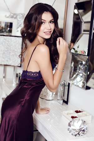 fashion interior photo of beautiful sensual woman with long dark hair wears elegant silk dress, posing at luxurious bedroom