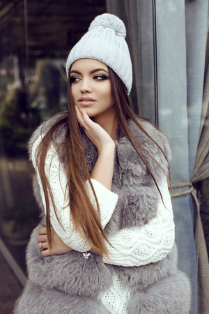 glamour hair: fashion street outfit, beautiful glamour girl with dark straight hair wears luxurious fur coat and knitted hat