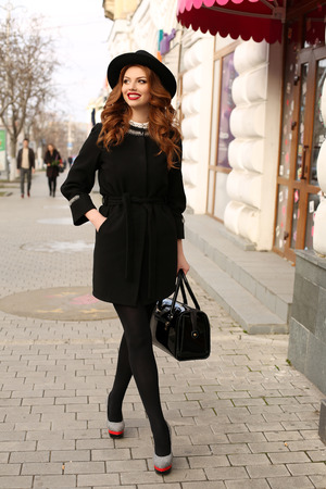 woman bag: fashion photo of beautiful young woman with dark curly hair and charming smile,wears elegant clothes,walking by street
