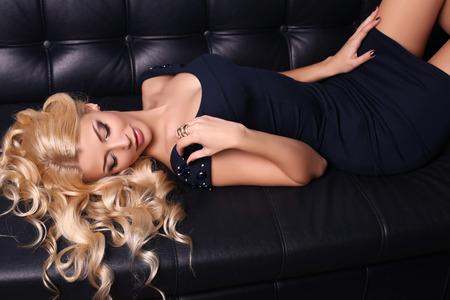 divan: estudio de moda foto de la hermosa mujer encantadora con el pelo largo y rubio que viste el vestido elegante y accesorios