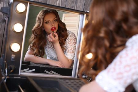 Fashion studio portret van mooie glamour meisje met donker krullend haar het maken van make-up, schildert haar lippen, op zoek naar spiegel Stockfoto