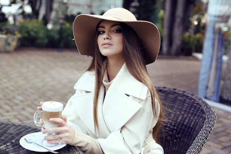 elegant girl: fashion street outfit, beautiful glamour girl with dark straight hair wears luxurious beige coat with elegant hat,drinking coffee in outdoor cafe Stock Photo