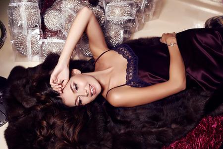 christmas deco: fashion interior photo of beautiful sensual woman with long dark hair wears elegant dress,lying on the floor beside Christmas deco