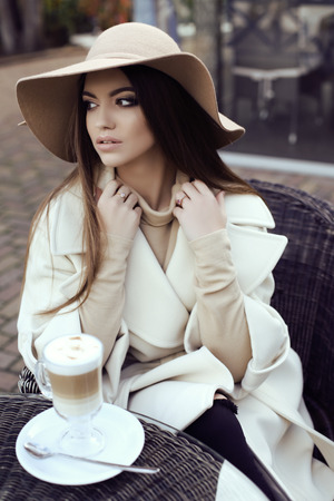 fashion street outfit, beautiful glamour girl with dark straight hair wears luxurious beige coat with elegant hat,drinking coffee in outdoor cafe
