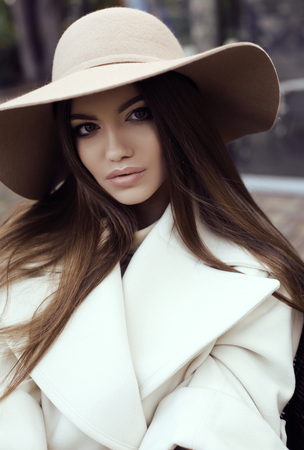elegant girl: fashion street outfit, beautiful glamour girl with dark straight hair wears luxurious beige coat with elegant hat