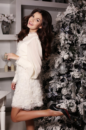 elegant girl: fashion interior photo of beautiful sensual woman with long dark hair wears elegant dress posing  beside decorated Christmas tree