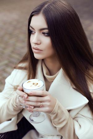 mujer elegante: traje de calle de la moda, la glamorosa muchacha hermosa con el pelo oscuro recto lleva escudo beige de lujo, el consumo de café en café al aire libre
