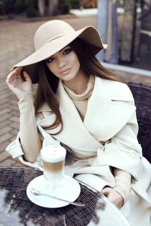 outdoor glamour: fashion street outfit, beautiful glamour girl with dark straight hair wears luxurious beige coat with elegant hat,drinking coffee in outdoor cafe Stock Photo